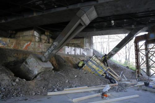 Sanace patek žel. mostu přes ulici Vršovická - patky se nejprve částečně obnažili a poté obetonováním zesílily.