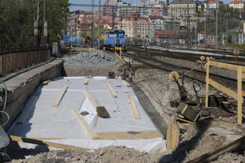 Most přes potok Botič po položení izolace spolu s pracovním vlakem stavby v pozadí.